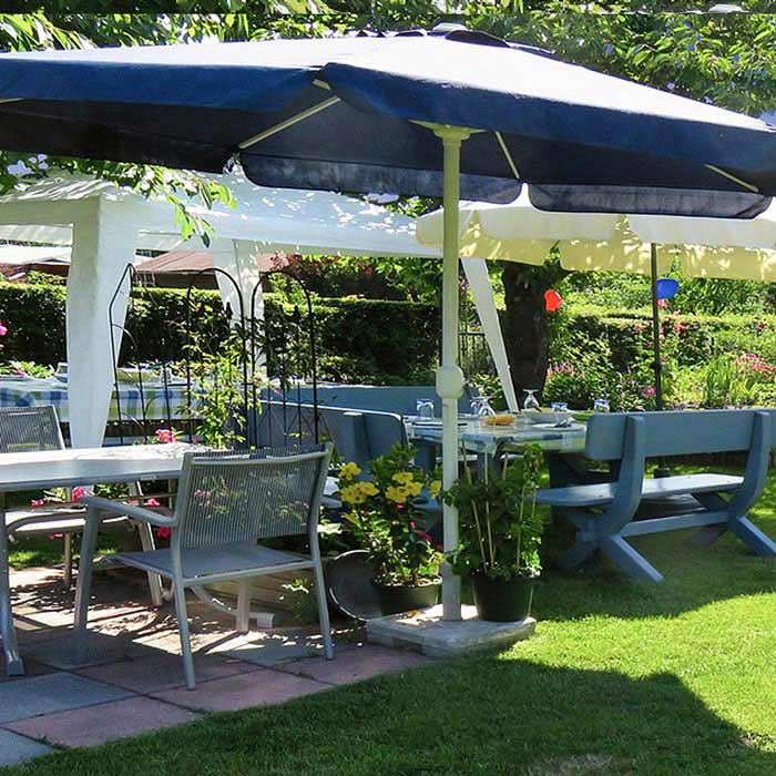 Un jardín con una gran sombrilla que cobija unas sillas y mesas expuestas al sol