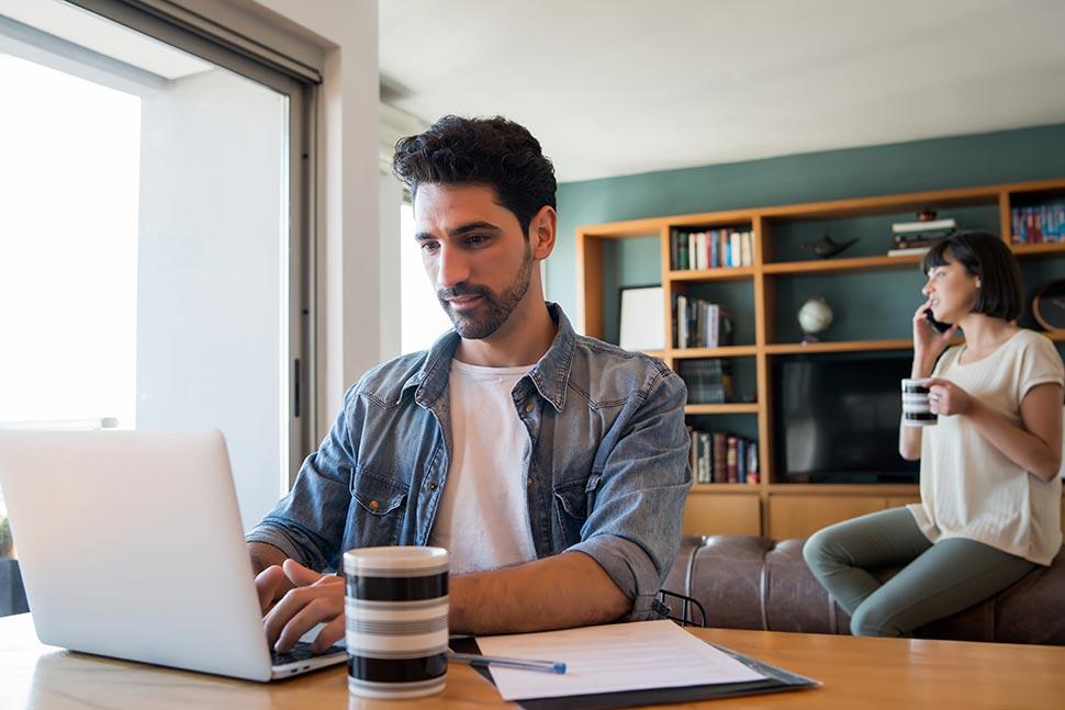 Hombre en ordenador y mujer habla por teléfono